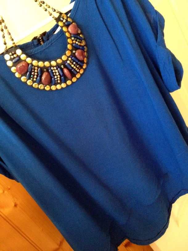 blue top and necklace